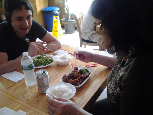 John instructs Celeste on proper chopstick usage before discretely backing away